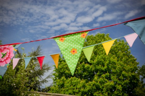 Beautiful home-made bunting with recycled material, hanging in front of trees and a blue sky.