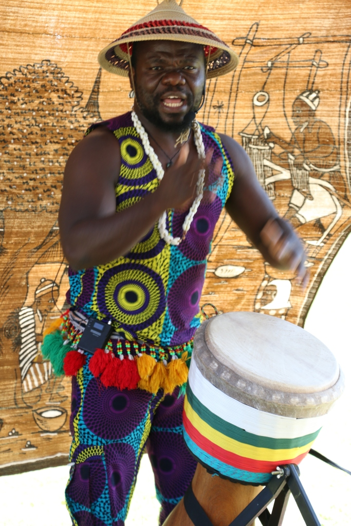 West African Master Drummer, Kofi Kunkpe, drumming in traditional costume.