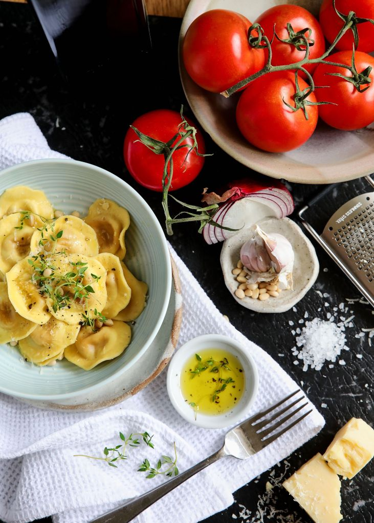 Photographs of fresh pasta, plump, red tomatoes in a bowl, garlic cloves, pine nuts, rock salt, olive oil, cheese and fresh thyme leaves laid out on a table, ready to eat.