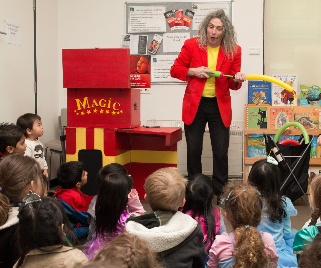 Magician in bright red jacket and yellow t-shirt does magic trick with bike pump and yellow balloon standing in front of children seated in a classroom.