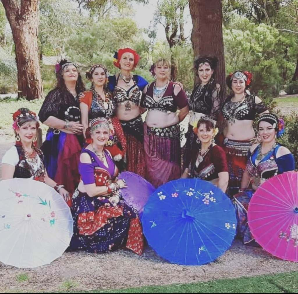 Melbourne Urban Bellydance Collective group photo with colourful costumes and sun umbrellas